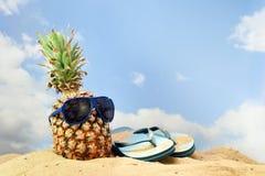 Fruit d'ananas avec des lunettes de soleil et des sandales de bascule électronique sur le bea Photographie stock libre de droits