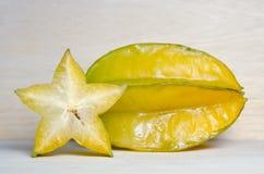Fruit de caïmite avec à moitié la section transversale d'isolement sur le verrat en bois Photographie stock