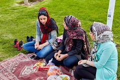 Fruit de casse-croûte de trois jeunes femmes sur la pelouse en parc, Iran Photo libre de droits