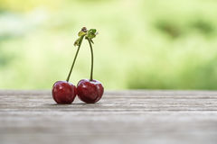 Fruit de cerise sur la table en bois au-dessus du fond de vert de bokeh photographie stock libre de droits