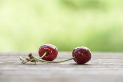 Fruit de cerise sur la table en bois au-dessus du fond de vert de bokeh images stock