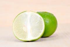 Fruit de citron ou de chaux avec à moitié la section transversale d'isolement sur b en bois Photos stock