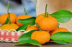 Fruit de mandarine avec la feuille verte sur le plancher en bois, concentré sur le milieu de l'orange avant Photo libre de droits