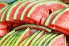 Fruit de pastèque coupé en tranches en morceaux sur le plancher en bois. Photographie stock libre de droits