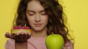 Fruit de pomme de participation de jeune femme et gâteau de baie sur le fond jaune banque de vidéos
