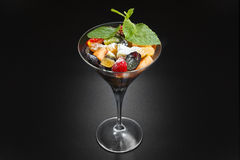 Fruit desert in the wineglass. Salad with pineapple orange kiwi grape Stock Images