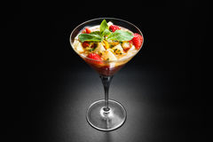 Fruit desert in the wineglass. Salad with pineapple orange passion fruit strawberry and mint in wineglass on dark background Stock Images
