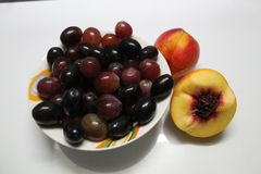 Fruit on dessert. Appetizing ripe sweet violet juicy grapes fruit and pulp peach for dessert stock photo