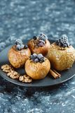 Fruit dessert baked apples stuffed with blackberry, blueberries, cinnamon, nuts, honey. royalty free stock photography
