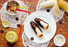 Fruit dessert for children from bananas, chocolate and dragee sh Royalty Free Stock Images