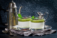 Fruit dessert green panna cotta. With mint in a glass over black background royalty free stock photo