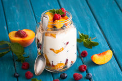 Fruit dessert in a mason jar. Fruit and berries dessert in a mason jar on blue table. Fruit salad with yogurt or sour cream Stock Photos