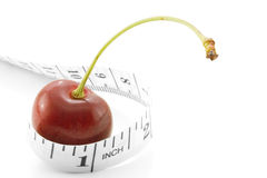 Fruit diet. Red Cherry with measuring tape royalty free stock images