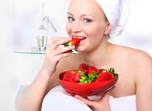 Fruit diet. Attractive girl with a bowl of ripe strawberries relaxes in the living room stock photography