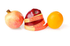 Fruit diet for weight lost. Red fresh apple wrapped up by tape with pomegranate and orange Stock Photos