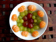 Fruit Dish. A well arranged fruit dish, served on a wooden table with grid pattern Stock Images