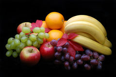Fruit display on black. Selection of various fruit, apples,oranges,grapes and bannanas stock image