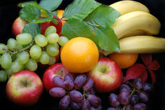 Fruit display on black. Selection of various fruit, apples,oranges,grapes and bannanas royalty free stock images