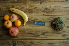 Fruit and donut with chocolate on a wooden background stock image