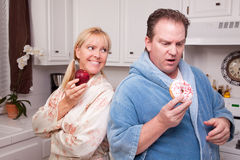 Fruit or Donut Healthy Eating Decision. Couple in Kitchen Eating Donut and Coffee or Healthy Fruit Stock Photos