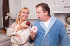 Fruit or Donut Healthy Eating Decision. Couple in Kitchen Eating Donut and Coffee or Healthy Fruit Royalty Free Stock Image