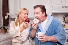 Fruit or Donut - Healthy Eating Decision. Couple in Kitchen Eating Donut and Coffee or Healthy Fruit Stock Photos