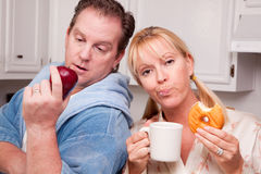 Fruit or Donut Healthy Eating Decision. Couple in Kitchen Eating Donut and Coffee or Healthy Fruit Royalty Free Stock Photography