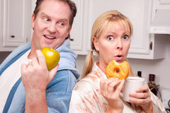 Fruit or Donut - Healthy Eating Decision. Couple in Kitchen Eating Donut and Coffee or Healthy Fruit Royalty Free Stock Images