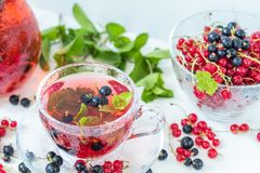 Fruit drink in transparent glass carafe and cup Stock Images
