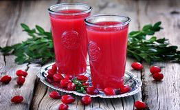 Fruit drinks from a cornel on the old wooden background. Royalty Free Stock Photos