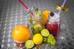 Fruit drinks with ice on metal background. Fruit drinks in glass cups with tubes with ice on metal background Royalty Free Stock Photography