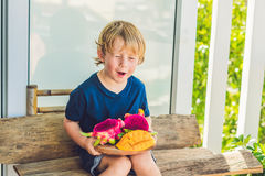 Fruit du dragon et mangue découpés dans les mains du garçon photos libres de droits