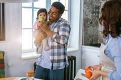 Fruit eathing de petite fille tout en étant prise dans des bras de son papa photos libres de droits