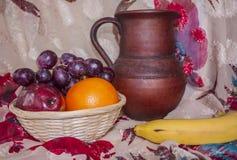Fruit in een mand, en aardewerkkruik Royalty-vrije Stock Afbeelding