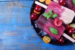 Fruit en bessenijslollys op de plaat met ijs, stukken van kumquat, kalk en kersen en munt royalty-vrije stock foto's