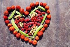 Fruit en forme de coeur sur le fond rayé en bois Image libre de droits