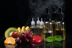 Fruit et saveurs dans des bouteilles pour une cigarette électronique, concept sur un fond noir avec une vapeur photographie stock libre de droits