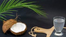 Fruit exotique de noix de coco, deux moitiés du fruit dans la coquille, un fond foncé, un verre de l'eau de noix de coco sur la c images stock