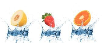 Fruit falling into water Stock Photos