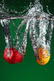 Fruit falling into water. Over green background stock photography