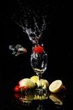 Fruit falling into water. Blank background, red tomatos falling into water in a goblet, peach, tomatoes, lemon on the desk, with their reflection, fish towards Stock Image