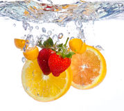Fruit falling into water. Clear ripple fresh red orange royalty free stock photos