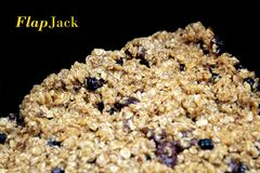 Fruit flapjack mix ready to bake in the oven, black background with copy space for text.  Royalty Free Stock Photography