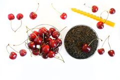 Fruit flavor favorite drink. Traditional black tea next to red cherries and a festive candle on a white background. View from above stock photography