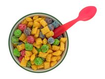 Fruit flavored breakfast cereal in a bowl with a red spoon. Top view of a bowl of generic fruit flavored breakfast cereal with a red plastic spoon handle in the stock image