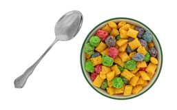 Fruit flavored breakfast cereal in a bowl with a spoon to the side. Top view of a bowl of generic fruit flavored breakfast cereal with a spoon to the side stock photo