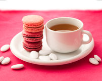 Fruit flavored macarons with a cup of tea Stock Image
