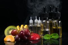 Fruit and flavors in bottles for an electronic cigarette, concept on a black background with a steam. Fruit and flavors in bottles for an electronic cigarette royalty free stock photography