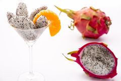 Fruit flesh of the Pitahaya blanca in a glass. The juicy pulp of the Pitahaya blanca presented in a glass and decorated with a mandarine slice. This exotic fruit Royalty Free Stock Image