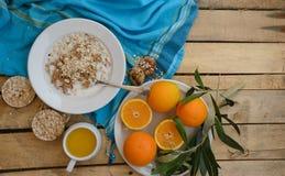 Fruit, flocons d'avoine, lait et jus d'orange sur la table en bois Photos stock